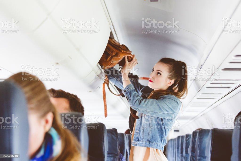 Weibliche Flugzeug Passagier Handtasche im Spind speichern Lizenzfreies stock-foto