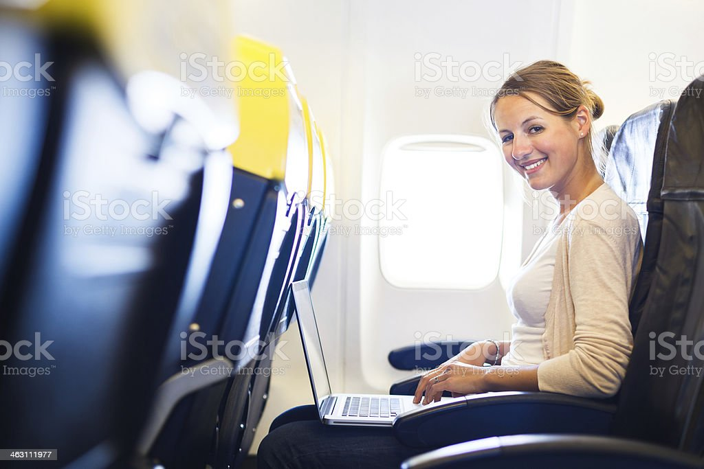 Female airplane passenger working on her laptop computer stock photo