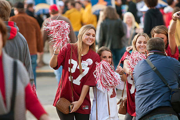 Female Alabama Fans Pose For Photo Outside Georgia Dome Atlanta, GA, USA - December 6, 2014:  Female University of Alabama fans dressed in crimson pose for a photo as they walk toward the Georgia Dome to watch the SEC Championship game against Missouri. ncaa college football stock pictures, royalty-free photos & images