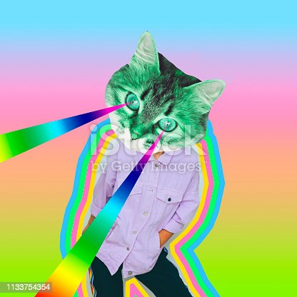 istock Female alien model with the cat head and rainbow lasers from the eyes on psychedelic background. 1133754354