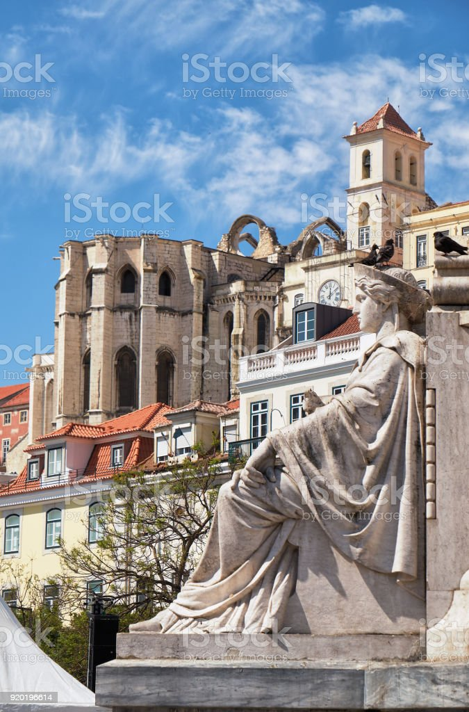 Female allegorical figure with Carmo Convent at the background. Rossio Square. Lisbon, Portugal stock photo