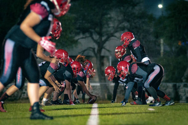 Female American Football Team Training Amateur Female American Football Team Training at dusk line of scrimmage stock pictures, royalty-free photos & images
