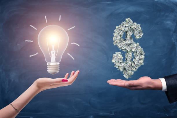 A female and a male hands holding a large bright light bulb and a dollar sign made of many money bills.