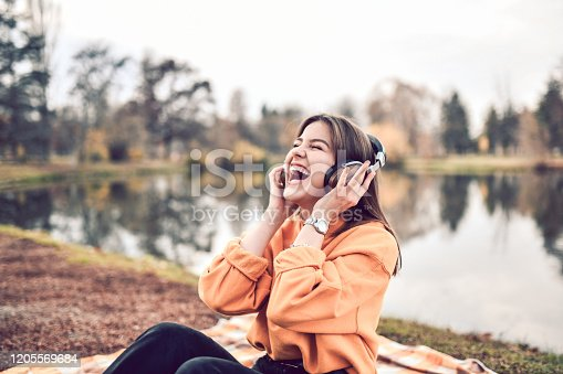 Female And Her Favorite Headphones By The Park Lake