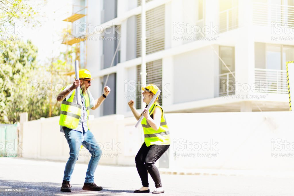 A man and a woman, both wearing protective work gear, stand cheering...