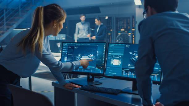 weibliche und männliche ingenieure diskutieren den 3d-cad-software-render eines elektrischen concet-autos. high-tech-labor mit einem prototypen-fahrzeug-chassis. - prototype stock-fotos und bilder