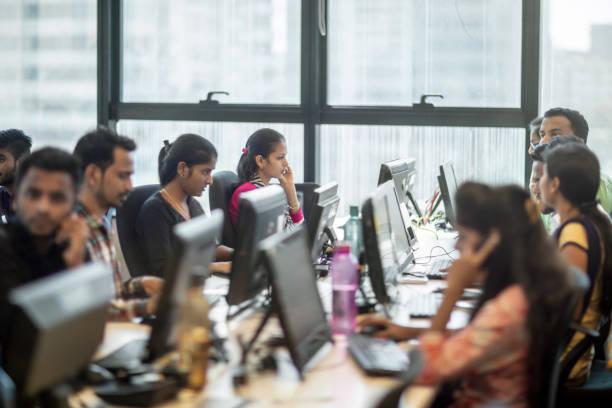 Unternehmerinnen und männliche Unternehmer am Schreibtisch – Foto