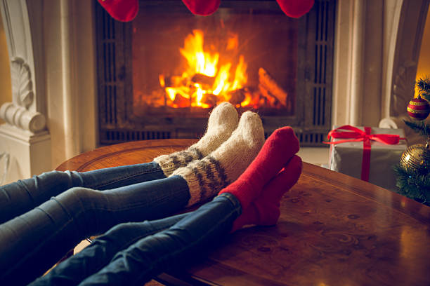 Female and male feet in wool socks warming at fireplace Closeup toned image of female and and feet in wool socks warming at fireplace at chalet log fire stock pictures, royalty-free photos & images