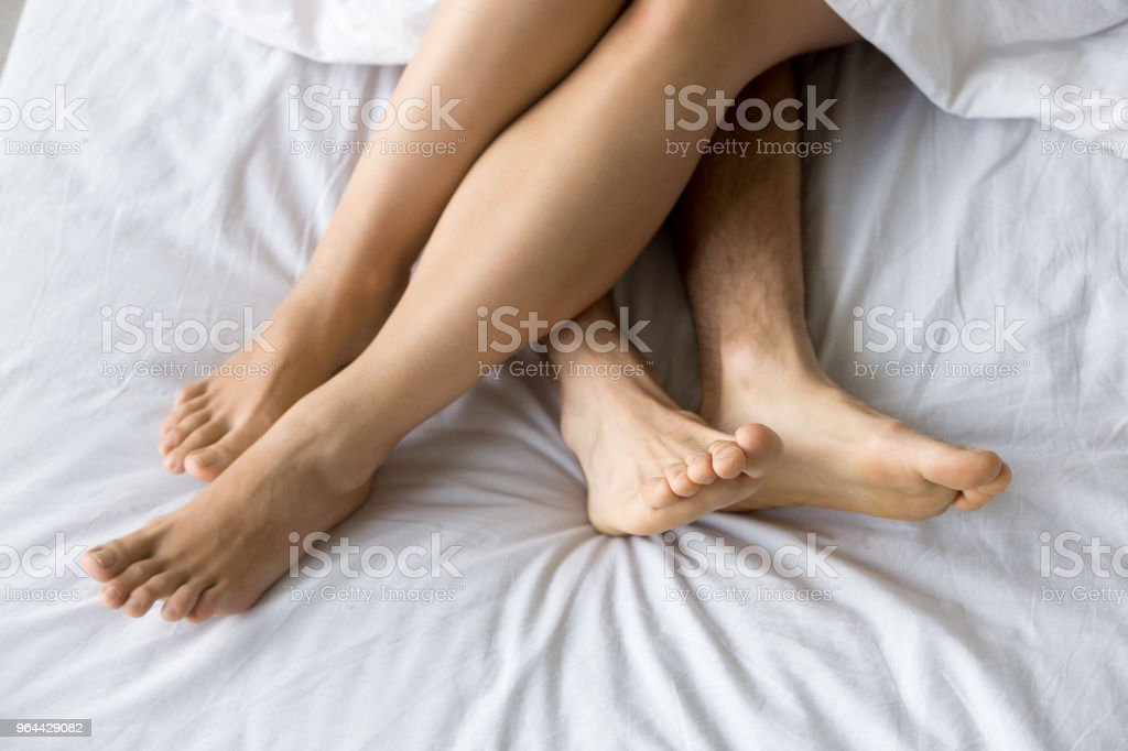 Female and male feet on comfortable bed, closeup top view - Royalty-free Adult Stock Photo