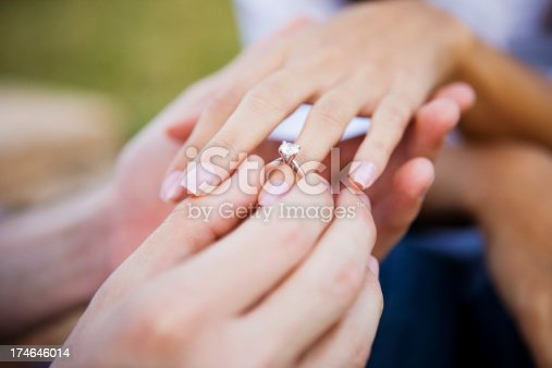 Young man is seen slipping an engagement ring on his girlfriend's ring finger.