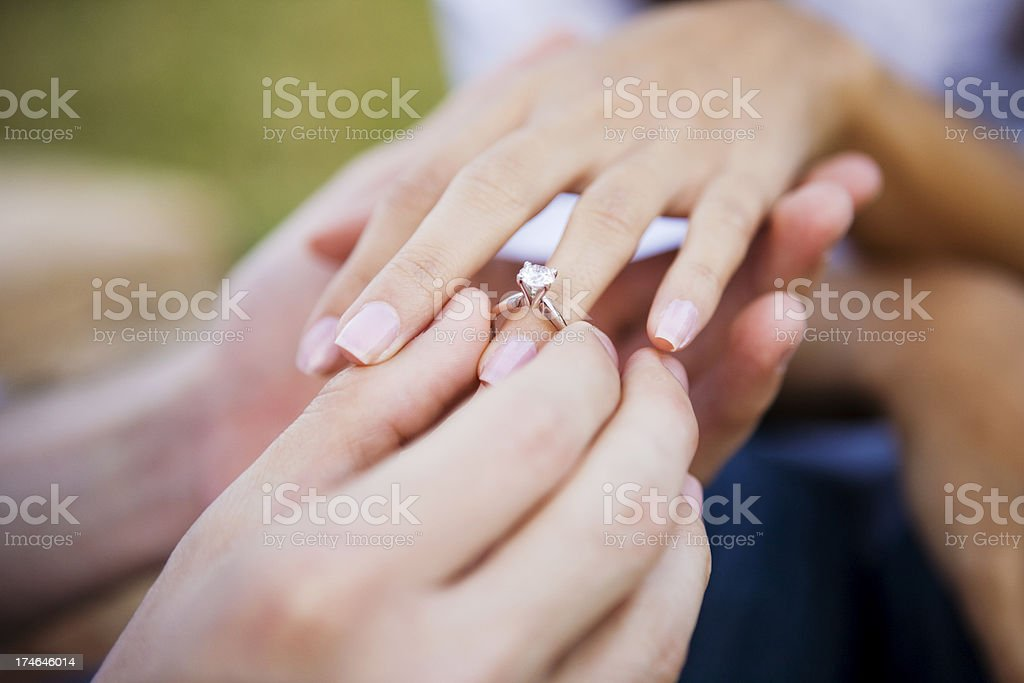 Female and male hands slipping on engagment ring stock photo