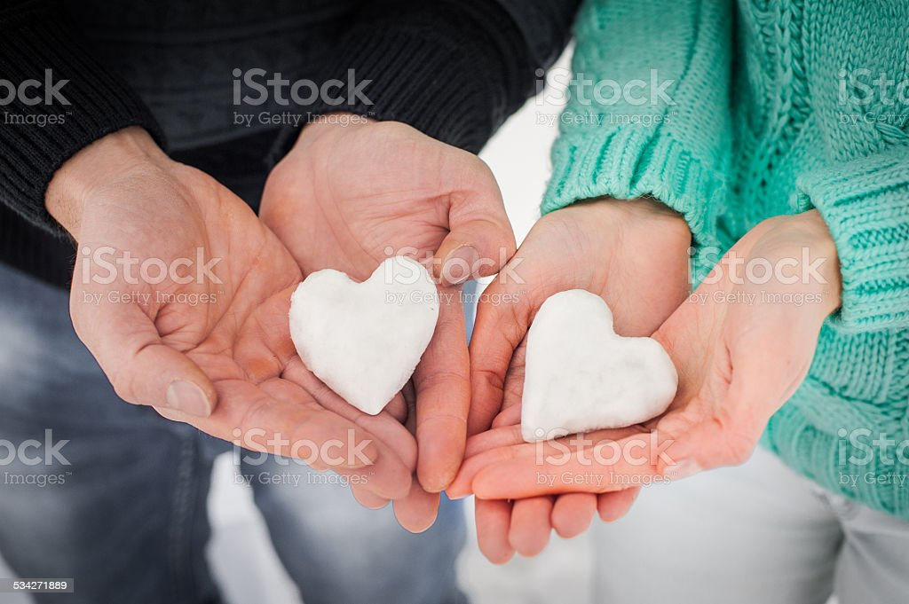 Female and male hands with snow hearts stock photo