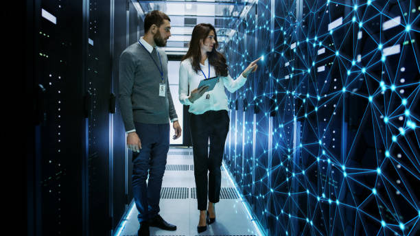 Female and Male IT Engineers Discussing Technical Details in a Working Data Center/ Server Room with Internet Connection Visualization. stock photo