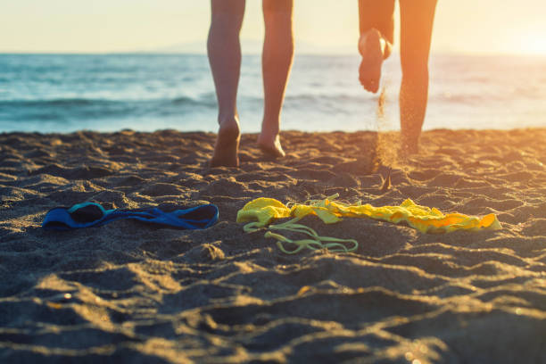 weibliche und männliche beine mit bikini und badehose auf dem sand auf einem sonnenuntergang hintergrund. - fkk strand stock-fotos und bilder