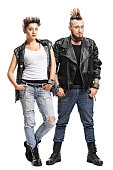 Full length portrait of a female and a male punker looking at the camera isolated on white background