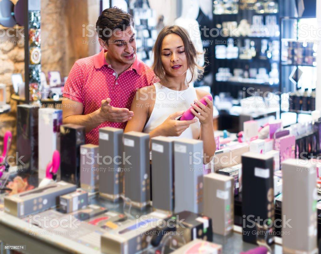 femininos e masculinos compradores tocando no sexo moderno loja diferentes brinquedos