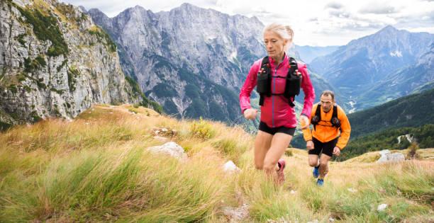 mujeres y hombres corredores corriendo colina en prado alto en las montañas - trail running fotografías e imágenes de stock