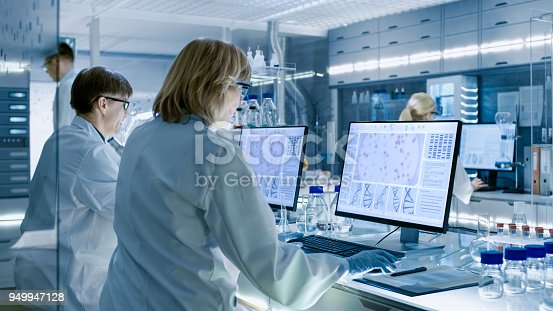 istock Female and Male Scientists Working on their Computers In Big Modern Laboratory. Various Shelves with Beakers, Chemicals and Different Technical Equipment is Visible. 949947128