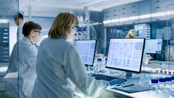 kobiety i mężczyźni naukowcy pracujący nad swoimi komputerami w dużym nowoczesnym laboratorium. różne półki z zlewkami, chemikaliami i innym sprzętem technicznym są widoczne. - laboratorium zdjęcia i obrazy z banku zdjęć