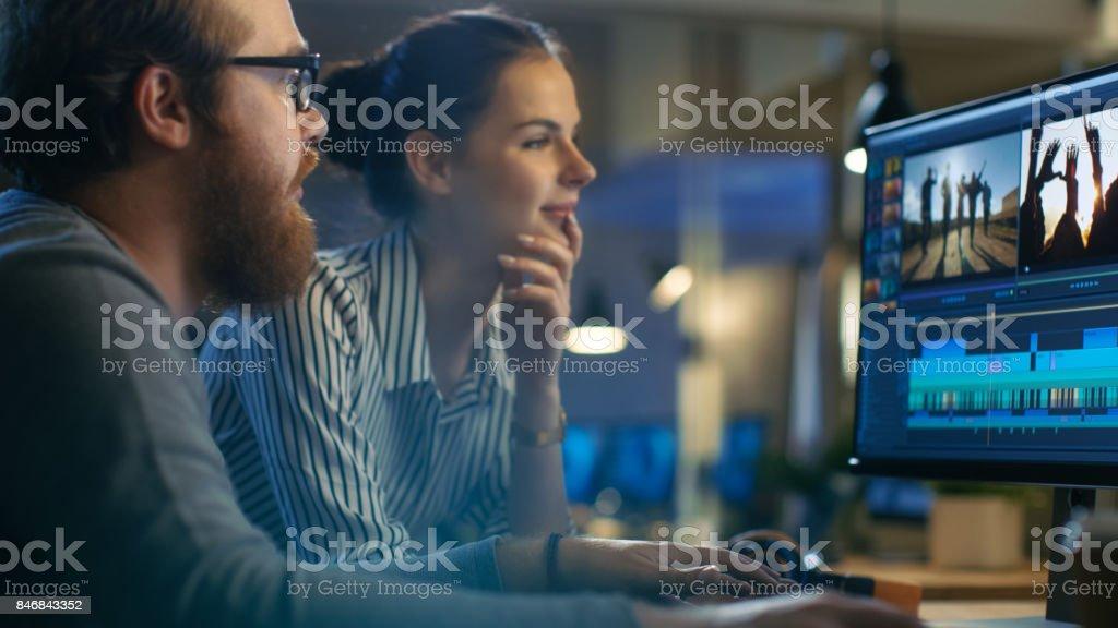 Editores de vídeo y trabajo con imágenes y sonido en su ordenador con dos pantallas. Son bellas y gente creativa y su oficina es Loft moderno. foto de stock libre de derechos