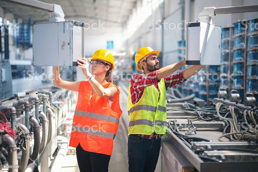 Female and male worker in factory using control panel stock photo