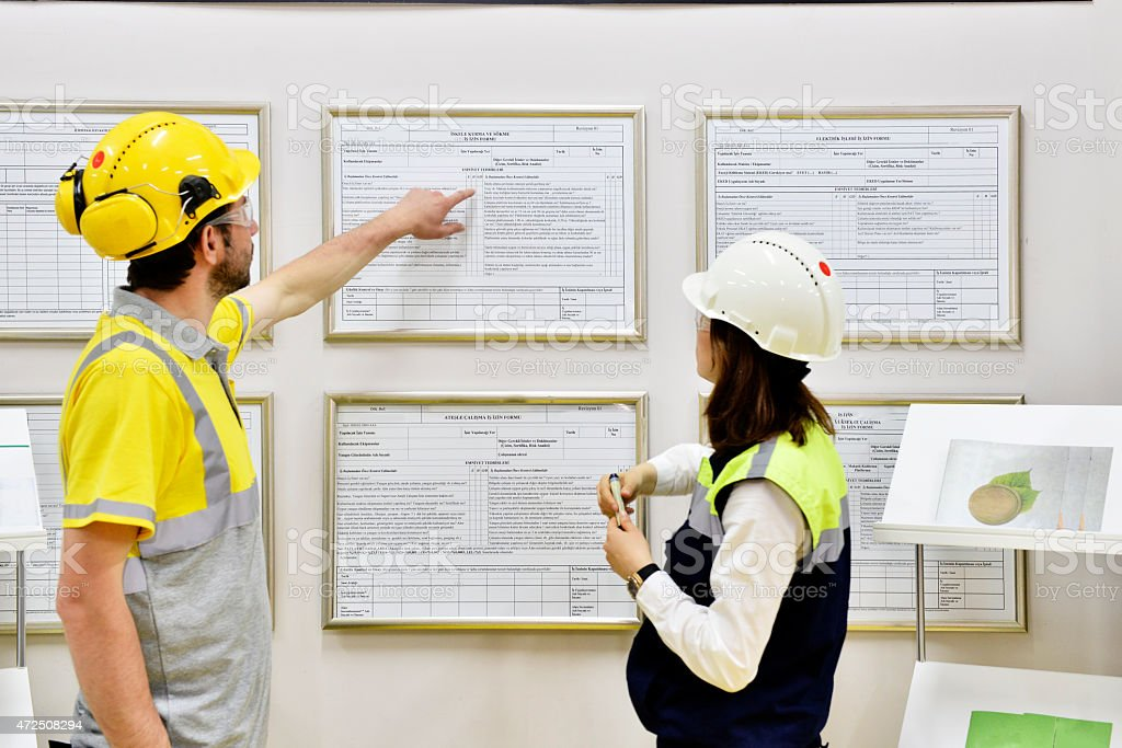 Female and male workers reading safety instructions stock photo