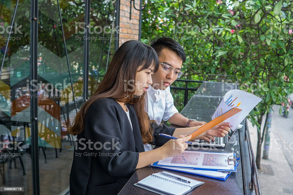 Female and male working together with documents at outdoor space stock photo