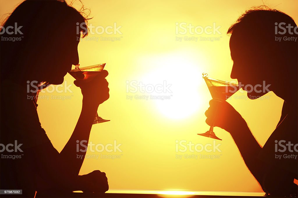 Female and man's silhouettes on sunset drink from glasses royalty-free stock photo