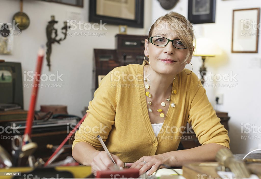 Female antique shop owner in store stock photo