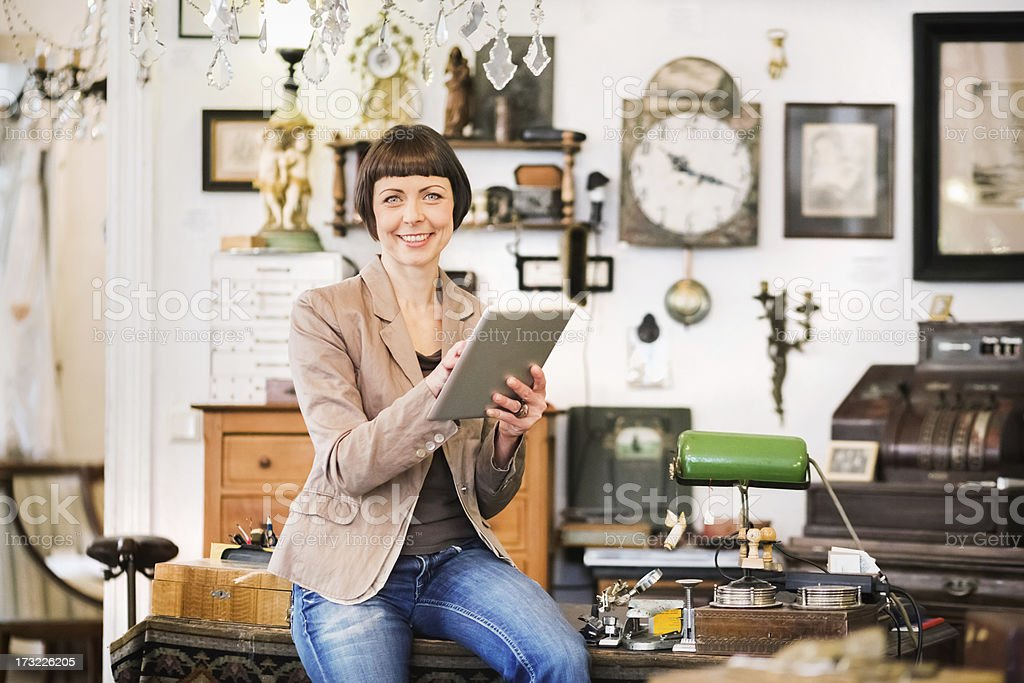 A female antique store owner using a tablet stock photo
