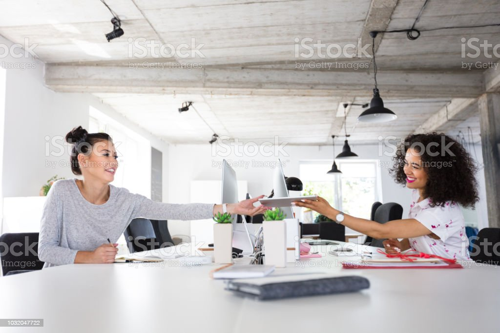 Female  application developers sharing data in office Young hispanic woman sharing some data on the digital tablet with colleague. Two business woman working around the table in modern work place. Adult Stock Photo