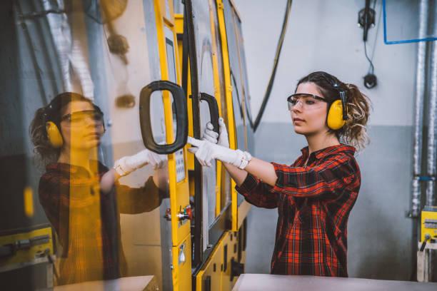 vrouwelijke leerling ingenieur werken met cnc machine in de fabriek - cnc machine stockfoto's en -beelden