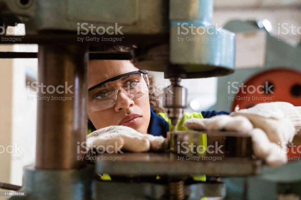 Female apprentice using yoke machine in factory Close-up of female apprentice using yoke machine. Female engineer is wearing protective glasses in factory. She is working in manufacturing industry. 30-34 Years Stock Photo