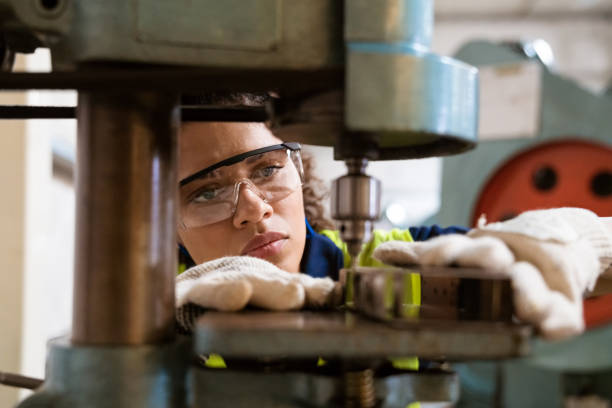 Female apprentice using yoke machine in factory Close-up of female apprentice using yoke machine. Female engineer is wearing protective glasses in factory. She is working in manufacturing industry. manufacturing stock pictures, royalty-free photos & images