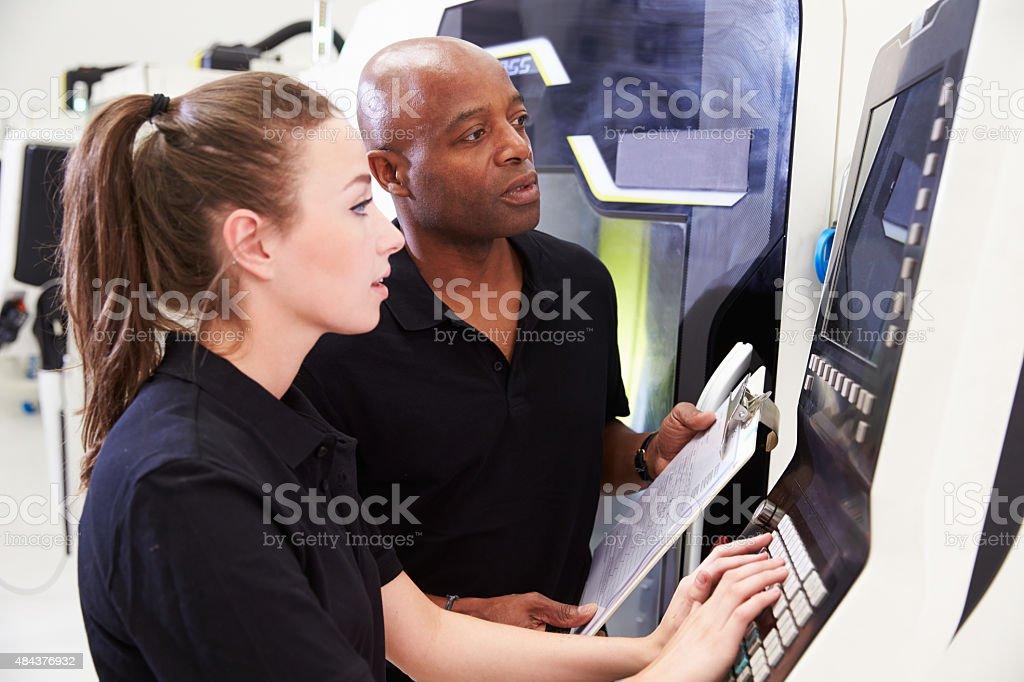Weibliche Engineer arbeiten mit Auszubildende auf CNC Machinery – Foto