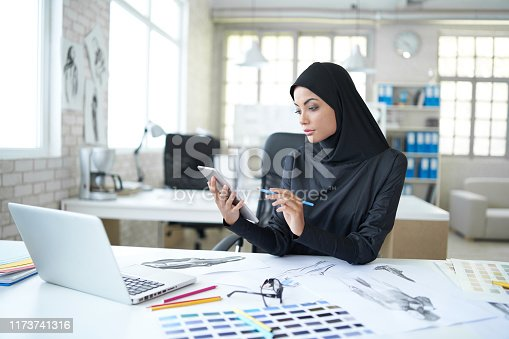 Female arab fashion designer creating new models using digital tablet and laptop