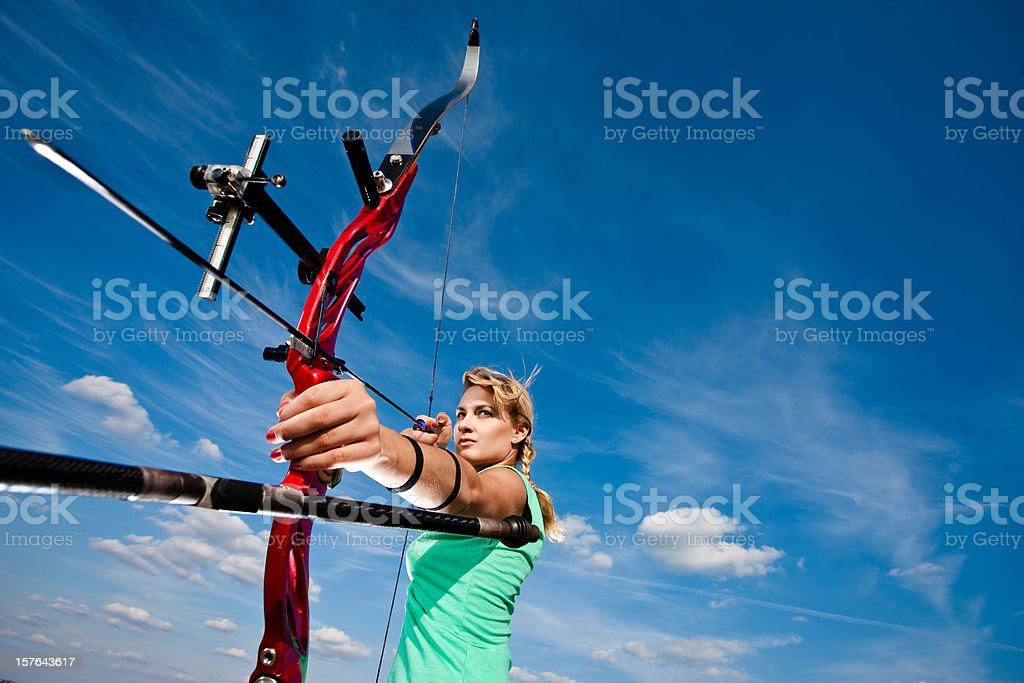 A female archer getting ready to release the arrow stock photo