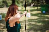 Young redhead woman practicing archery in the field