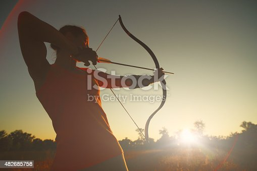 istock Female archer in the field at sunset 482685758