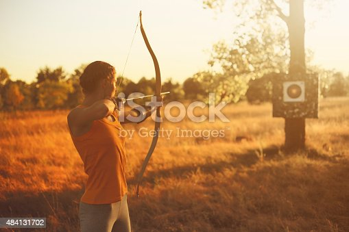 istock Female archer in the field at sunset 484131702