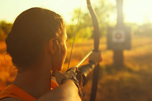 female archer in the field at sunset - sports target stock photos and pictures