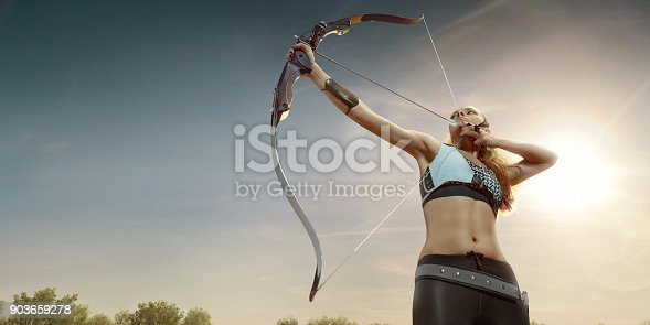 istock Female archer shooting with the longbow at sunset 903659278