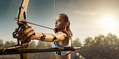 Female archer shooting with the longbow at sunset. Archer in professional field with a lot of fans.