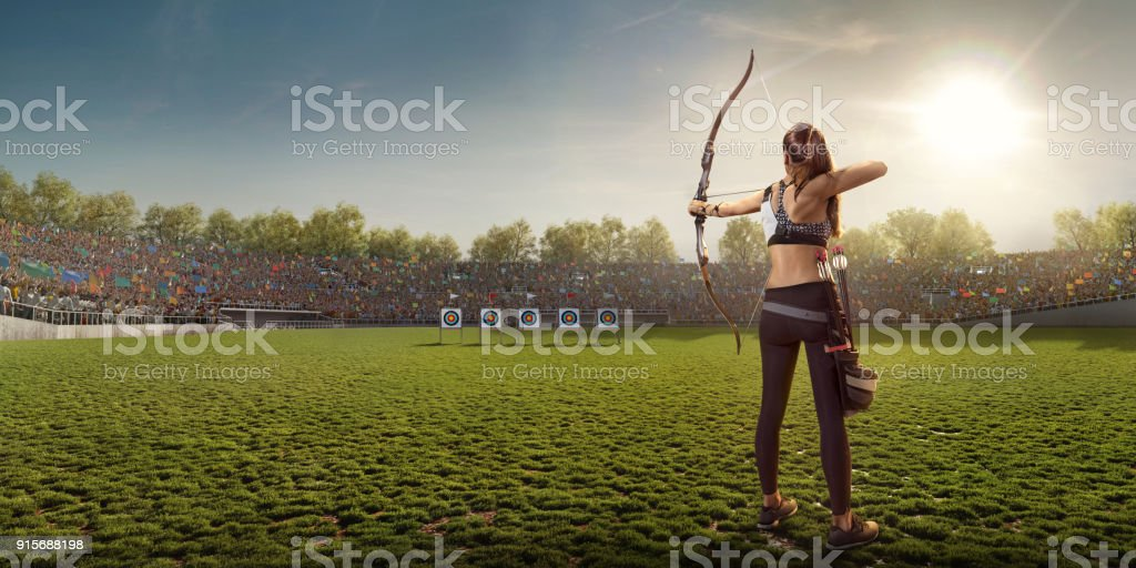Female archer shooting with the longbow at sunset stock photo