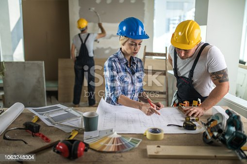 891274328 istock photo Female architect and construction worker examining housing plan during renovation process. 1063248304