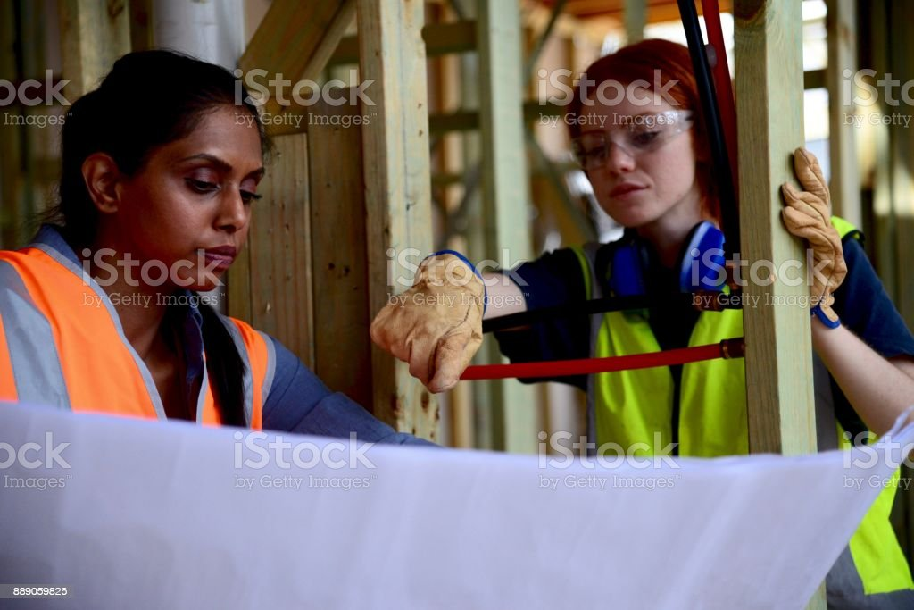 Female architect and female Construction worker discussing plans