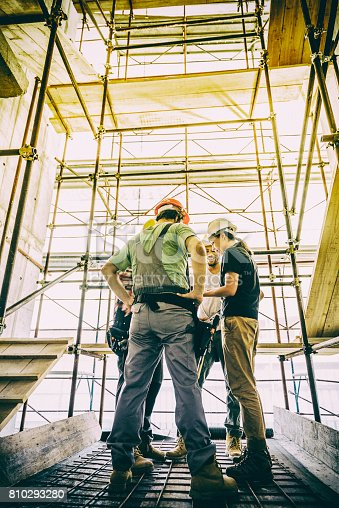 istock Female architect and three consruction workers on a construction site 810293280