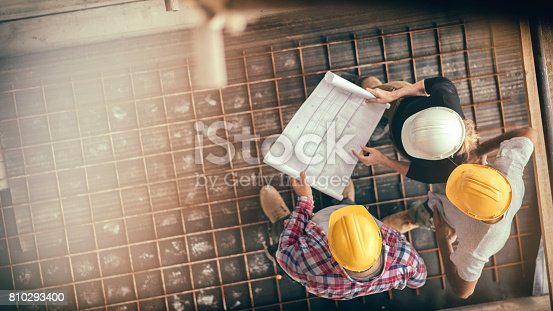 High angle view of three people with helmets, female architect, foreman and engineer on a construction site, looking down on a blueprint, copy space.