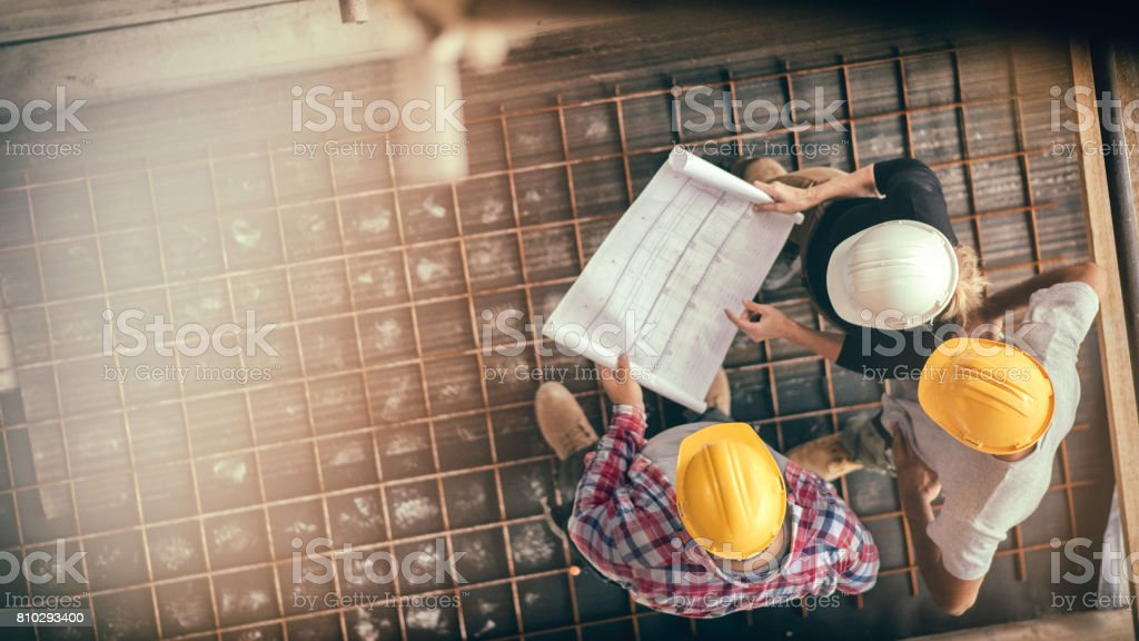 Female architect and two consruction workers on a construction site stock photo