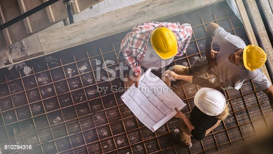 istock Female architect and two consruction workers on a construction site 810294316